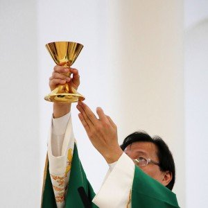 priest_holdingup_chalice_red